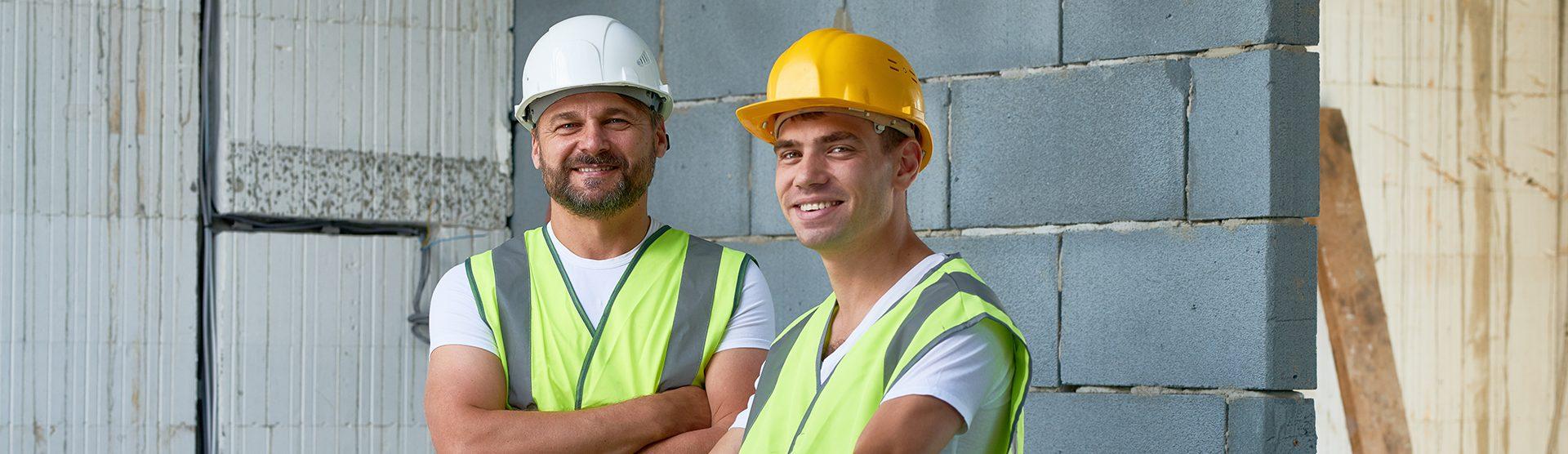 Twee lachende mannelijke bouwvakkers op de bouwplaats
