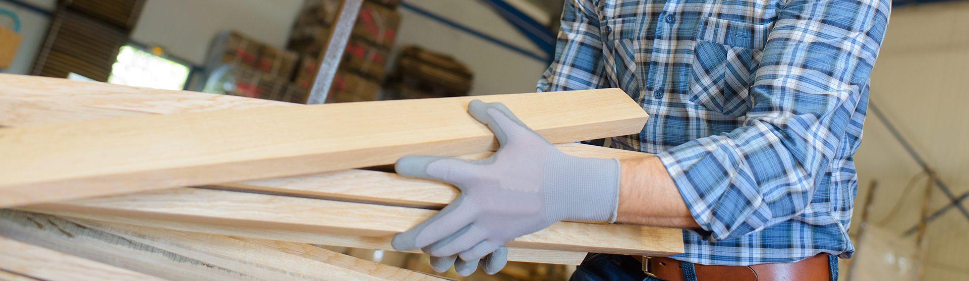 Een man met werkhandschoenen aan verplaatst hout in de werkplaats