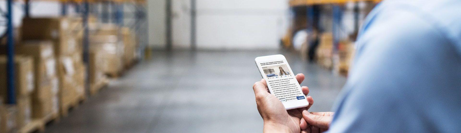 Een mannelijke werknemer bekijkt op zijn werk contextMe op zijn iphone.